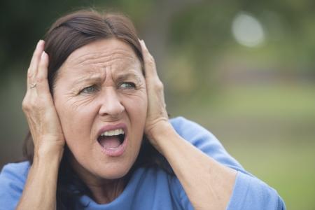 femme triste: Portrait jolie femme mature qui couvre frustr�s, en col�re ou de l'anxi�t� ses oreilles avec les mains, a soulign� choqu�, isol� avec un fond plein air floue. Banque d'images