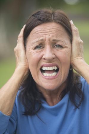 ansiedad: Retrato atractiva mujer madura que cubre frustrado, enojado o en la ansiedad de las orejas con las manos, molesto subrayado, aislado con el fondo al aire libre borrosa.