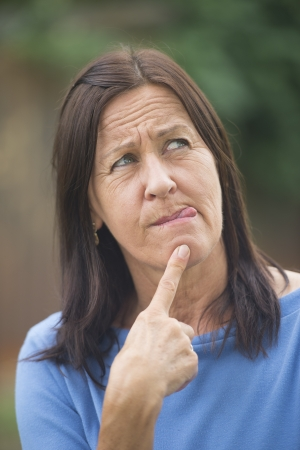 Portrait attractive mature woman outdoor with worried facial expression, thoughtful, troubled look, finger at chin and tongue out, isolated with copy space and blurred background. photo