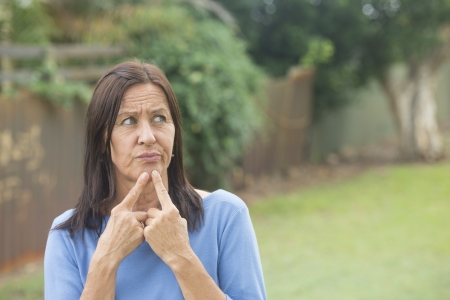 Portrait attractive mature woman outdoor with worried facial expression, thoughtful, troubled look, finger at chin, isolated with copy space and blurred park background. photo