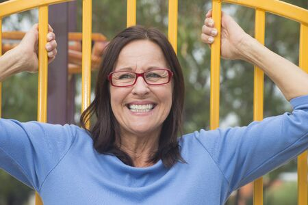glass fence: Portrait confident and happy relaxed smiling attractive mature woman outdoor with glasses, joyful and cheerful and blurred background Stock Photo