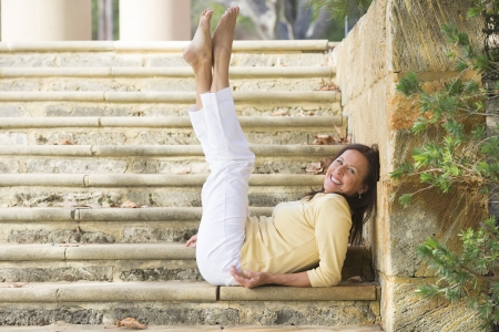 Portrait attractive, fit and healthy mature woman sitting confident relaxed and happy smiling with legs stretched up on limestone steps in park outdoor with copy space.
