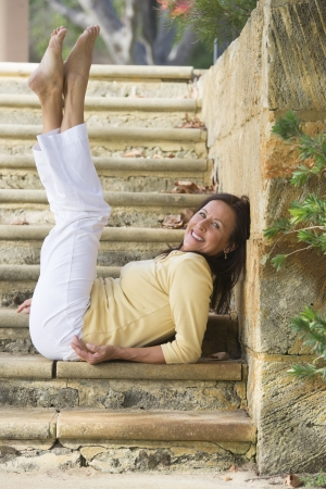 Portrait beautiful, fit and healthy mature woman sitting confident relaxed and happy smiling with legs stretched up on limestone steps in park outdoor with copy space.