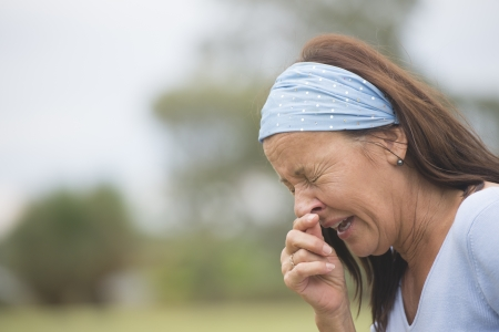 hayfever: Portrait attractive mature woman outdoor suffering from seasonal hayfever or cold ro flu, sneezing, with hand on nose, closed eyes, with blurred background and copy space.