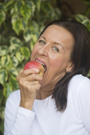 mature brunette: Portrait beautiful mature woman eating red apple, keeping up nutrition and vitamins, healthy and fit , blurred background outdoor.