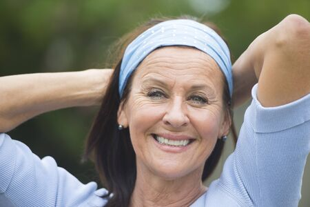 mature woman: Portrait attractive looking mature woman cheerful, joyful happy smiling outdoor, wearing blue shirt and headband, arms behind neck, blurred background.