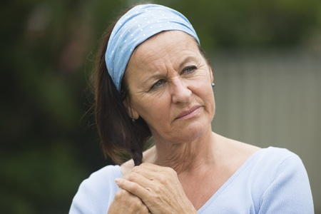 thoughtful woman: Portrait attractive mature woman with thoughtful, worried and depressed facial expression alone outdoor, wearing blue shirt and headband, with blurred background. Stock Photo