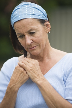 Portrait attractive senior woman with thoughtful, worried and depressed facial expression alone outdoor, wearing blue shirt and headband, with blurred background. photo