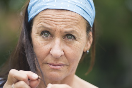 Close Up portrait attractive mature woman with thoughtful, worried facial expression outdoor and blurred background. photo