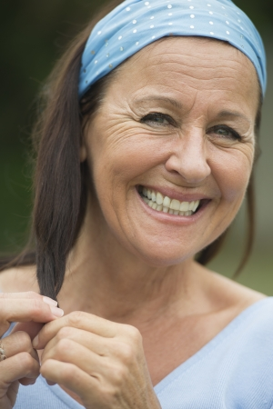woman face close up: Portrait happy funny smiling attractive mature woman outdoor, joyful facial expression, enjoying retirement and leisure lifestyle, wearing blue shirt and headband, with blurred background.