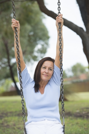 Portrait happy relaxed and beautiful looking mature woman sitting on swing on playground outdoor alone, with smile, blurred background of park photo
