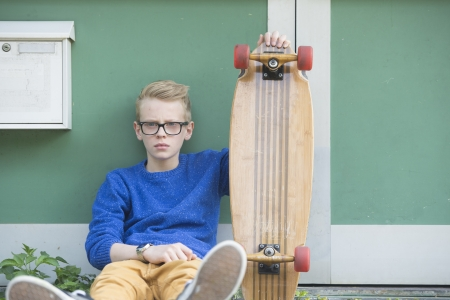Portrait of blond teenage boy outdoor with serious face, wearing glasses and holding his skateboard. photo
