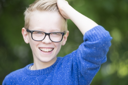 Portrait happy funny smiling confident blond teenage boy outdoor, wearing glasses, with blurred background. photo