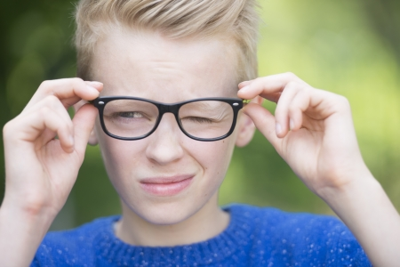 Portrait smart looking blond teenager with glasses and a blink of an eye, thoughtful and clever Stock Photo