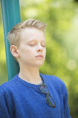 Portrait thoughtful and relaxed young blond teenage boy outdoor with closed eyes, concentrated and meditating, with blurred background. photo