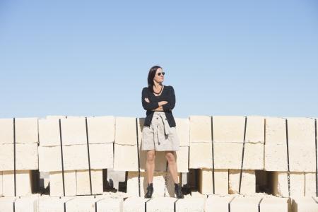 bas r�sille: Portrait sexy femme d'�ge m�r avec, portant la jupe, bas r�sille et bottes, est debout confiant, d�tendu sur le mur, avec le ciel bleu clair comme fond et de copier l'espace. Banque d'images