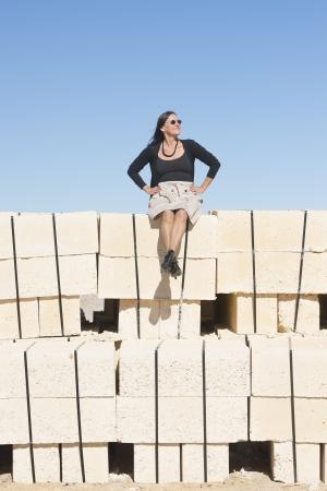 bas r�sille: Portrait sexy femme d'�ge m�r avec, portant la jupe, bas r�sille et des bottes, est assis confiant, d�tendu sur le mur, isol�, avec ciel bleu en arri�re-plan et l'espace de copie. Banque d'images