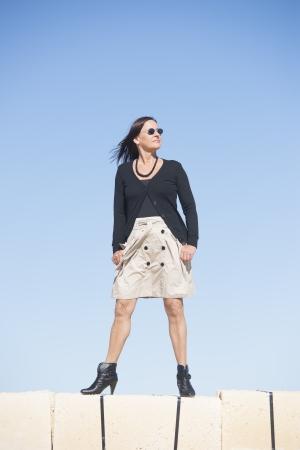 bas r�sille: Portrait de femme sexy mature avec jupe porter, bas r�sille et bottes, est debout confiant, d�tendu sur le mur, isol� avec un ciel bleu clair comme arri�re-plan et l'espace de copie. Banque d'images