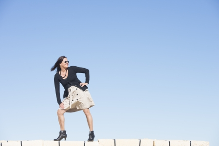 bas r�sille: Portrait heureux femme mature sexy avec jupe porter, bas r�sille et des bottes, est debout confiant, d�tendu et amical sur le mur, isol�, avec ciel bleu en arri�re-plan et l'espace de copie