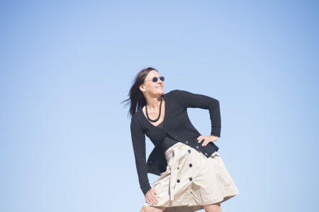 fishnets: Confident happy relaxed mature woman posing outdoor, wearing skirt, fishnet stockings, sunglasses, isolated with blue sky as background and copy space Stock Photo