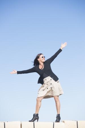 bas r�sille: Portrait heureux femme mature sexy avec les bras, portant une jupe, bas r�sille et bottes, est debout confiant, d�tendu et joyeux sur le mur, isol�, avec ciel bleu en arri�re-plan et l'espace de copie