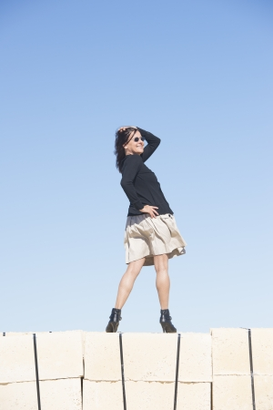 Portrait happy sexy mature woman wearing skirt, fishnet stockings and boots, is standing confident, relaxed and friendly on wall, isolated with clear blue sky as background and copy space  photo