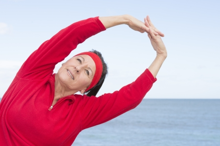 beautiful middle aged woman: Portrait beautiful middle aged woman showing active retirement, stretch exercising arms up outdoor, positive, confident, smiling, with ocean and cloudy sky as background and copy space  Stock Photo
