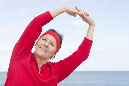 Ritratto attraente donna matura che mostra il pensionamento attivo, esercitando allungare le braccia spazio esterno, positivo, fiducioso, sorridente, con mare e cielo nuvoloso come sfondo e copia