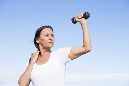 determined: Portrait beautiful confident mature woman exercising with weights, keeping healthy and fit, focused view, determined, positive, successful, with blue sky as background and copy space.