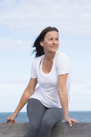 mature brunette: Portrait attractive sporty, fit and healthy mature woman sitting relaxed and happy on wooden handrail at sea, with ocean and sky as blurred background and copy space.