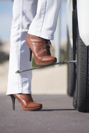 break down: Detailed image Stressed woman in high heel boots with car breakdown, trying to change tyre at vehicle on remote road, with blurred background and copy space. Stock Photo