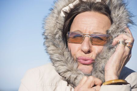 cold weather: Portrait attractive mature woman wearing warm jacket with hood and sunglasses, feeling cold and freezing, with blue sky as background and copy space.