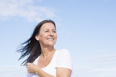 energetic people: Portrait attractive mature woman joyful and happy retired, keeping healthy and fit, isolated on blue sky background and with copy space.