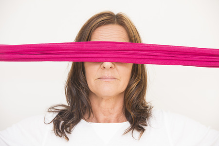 Portrait of attractive mature woman blindfolded with pink ribbon, posing with covered eyes, isolated on white background. photo