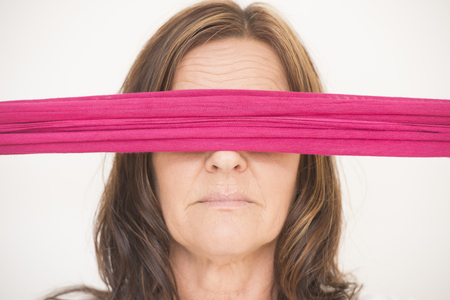 seductive women: Portrait of attractive middle aged woman blindfolded with pink ribbon, posing with covered eyes, isolated on white background.