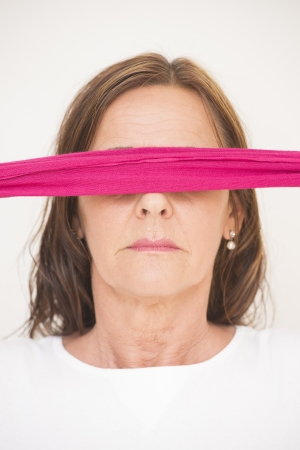 Portrait of attractive middle aged woman blindfolded with pink ribbon, posing with covered eyes, isolated on white background. photo