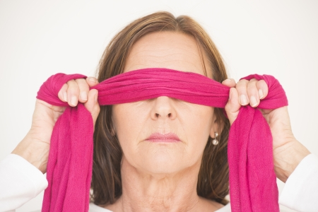 Portrait of attractive mature woman blindfolded with pink ribbon, posing with covered eyes and hands up, isolated on white background. Stock Photo - 22403912