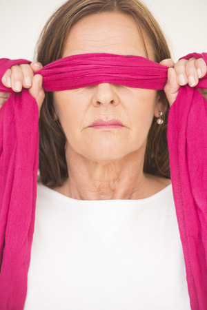 Portrait of attractive mature woman blindfolded with pink ribbon, posing with covered eyes and hands up, isolated on white background. photo