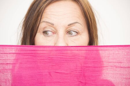 Portrait attractive mature woman hiding behind pink cloth, with sad concerned view and beautiful eyes, white background. photo