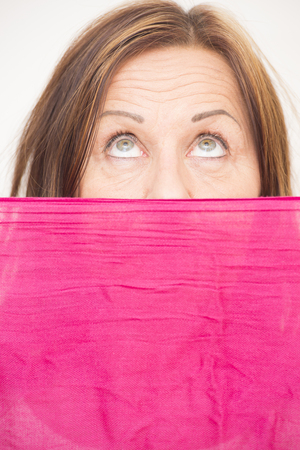 Portrait attractive mature woman hiding behind pink cloth, with upward view and beautiful eyes, white background. photo