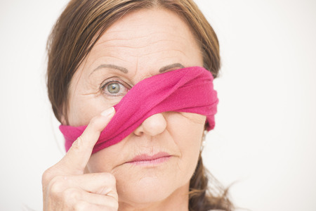Portrait attractive mature woman with blindfold covering one eye and sad concerned look, isolated on white background. photo