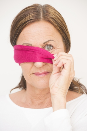 Portrait attractive mature woman with blindfold covering one eye and looking with straight confident view into camera, isolated on white background. photo
