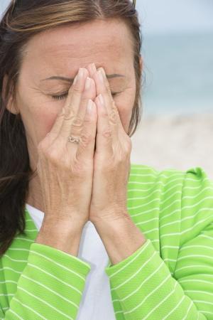 ojos llorando: Retrato atractiva mujer madura estresado, deprimido y en la pena, rezando con las manos cubriendo la cara.