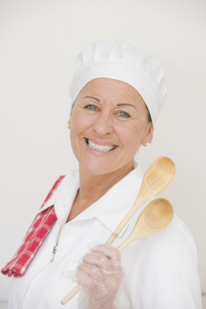 Portrait confident happy and attractive female cook in white chef workwear posing with towel over shoulder and wooden spoons in hand, isolated on white  photo
