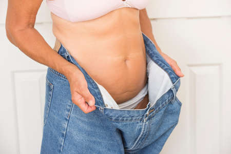 over sized: Torso of mature woman showing proud result of weightloss through successful dieting, wearing over sized jeans and bra, isolated on white.