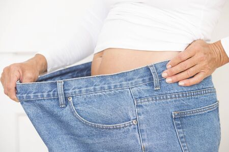 over sized: Torso of woman showing proud result of weightloss through successful dieting, wearing over sized jeans and shirt, isolated on white. Stock Photo