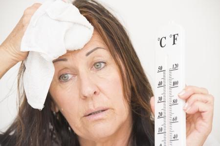sudoracion: Retrato atractiva mujer madura que sufre de calor, alta temperatura, fiebre, con gotas de sudor por el rostro y runing termómetro en la mano, aislados en blanco.