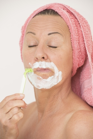 Portrait attractive funny mature woman with towel around head and closed eyes, shaving her face with lotion and razor, isolated on white. photo