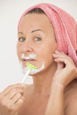 Portrait attractive relaxed mature woman with towel around head and happy smiling, shaving her face with lotion and razor, isolated on white. photo