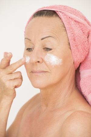 Portrait attractive mature woman moisturizing face with lotion and cream, with finger on cheek and towel around head, isolated on white. photo